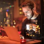 man-holding-mug-in-front-sorglos durch die Adventszeitof-laptop